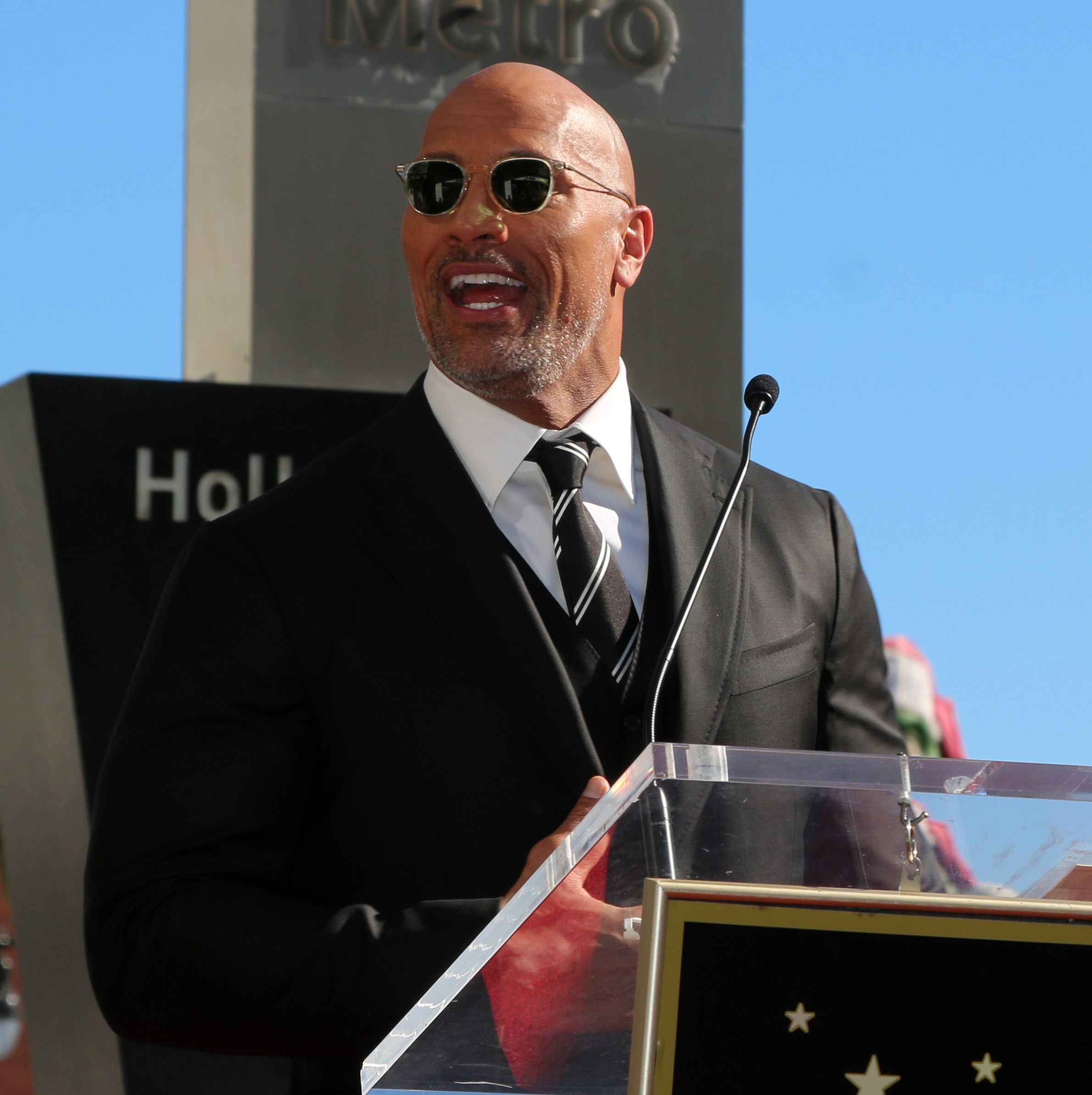Dwayne Johnson at podium making speech
